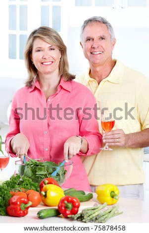Happy seniors couple cooking at new kitchen - stock photo
