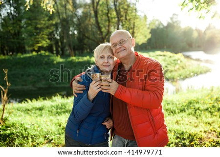happy seniors couple embrace and smile; older male and female in park have coffee break;