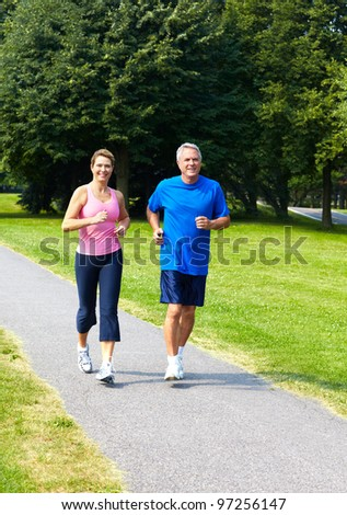 Happy seniors couple jogging in the park. - stock photo