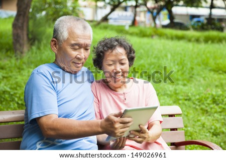 happy seniors couple with tablet pc in the park  - stock photo