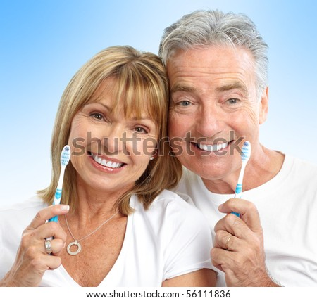 Happy seniors couple with toothbrushes. Healthy teeth. Over blue background - stock photo