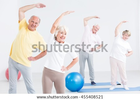 Happy seniors during workout for couples, light and spacious interior