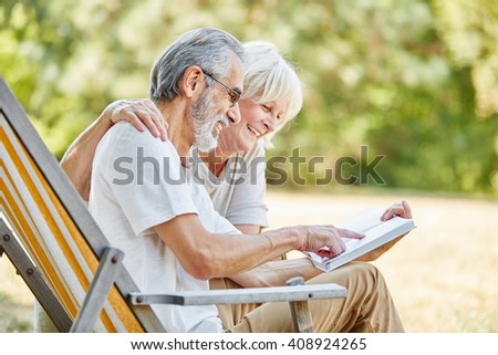 Happy seniors reading a book together in the nature in summer - stock photo