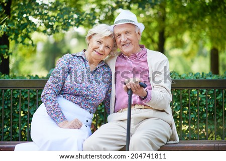 Happy seniors sitting on bench in the park and looking at camera - stock photo
