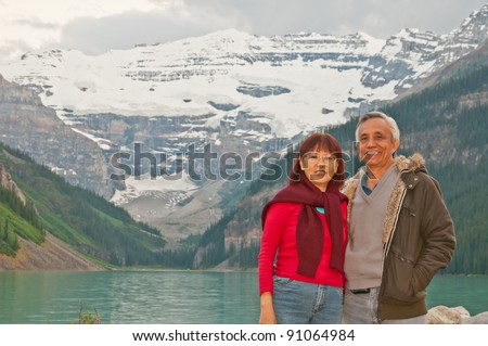 Happy seniors smiling during vacation to Lake Louise. - stock photo