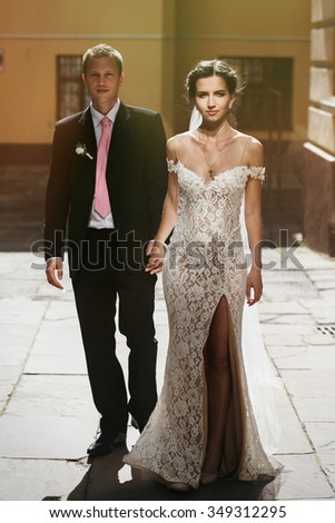 Happy sensual brunette bride with veil posing outdoors with groom in sunlit street - stock photo