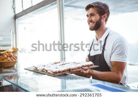 happy server holding pastry at the backery - stock photo