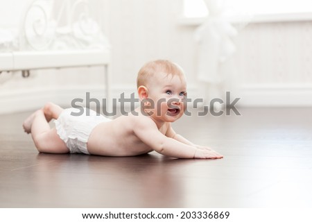 Happy seven month old baby girl crawling on a hardwood floor in living room  - stock photo
