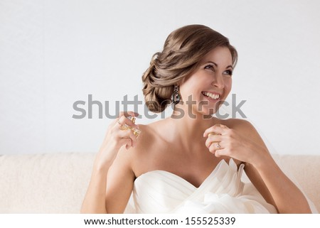 Happy sexy beautiful bride with perfume bottle. - stock photo