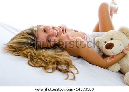 Happy sexy girl with teddy bear lays on a bed and relax - stock photo