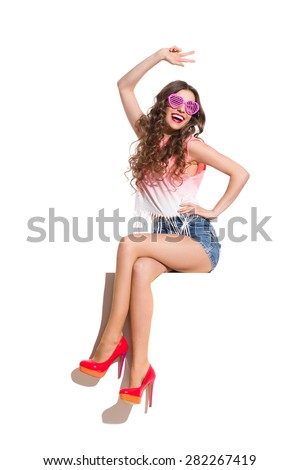 Happy sexy woman in pink sunglasses, pink top, jeans shorts and red high heels sitting on a top of the white banner, waving hand and showing peace sign. Full length studio shot isolated on white. - stock photo