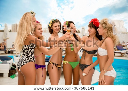 Happy sexy young  women clinking  glasses at bride's hen party  by the pool