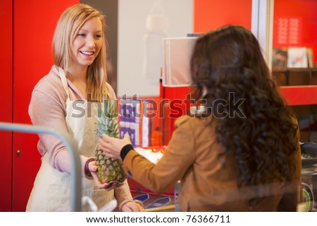 Happy shop assistant with customer in supermarket holding pineapple - stock photo