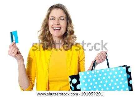 Happy shopaholic female laughing. Holding credit-card and shopping bags - stock photo