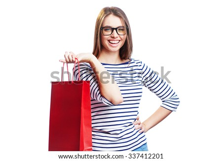 Happy shopaholic with paperbag looking at camera with smile