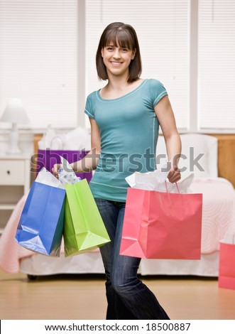 Happy shopper holding shopping bags - stock photo