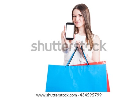 Happy shopper with shopping bags showing a blank smartphone screen with copyspace isolated on white background - stock photo
