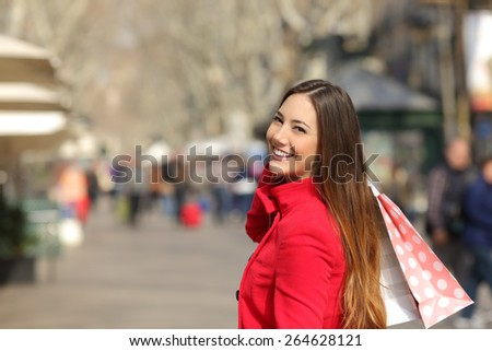 Happy shopper woman walking and shopping in the street in winter holding bags - stock photo