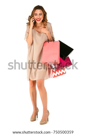 Happy shopper woman with bags talking on the phone on isolated white background