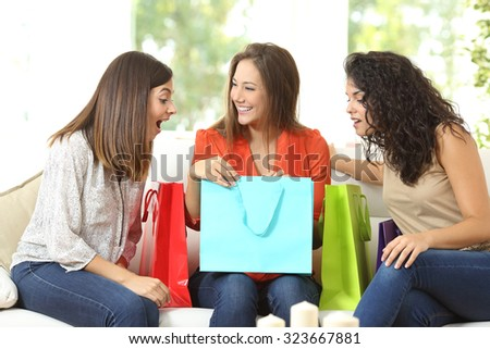 Happy shoppers with shopping bags talking sitting on a couch at home - stock photo
