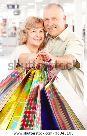Happy shopping elderly people in the mall - stock photo