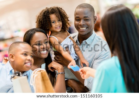 Happy shopping family at the cashier paying for their purchases - stock photo