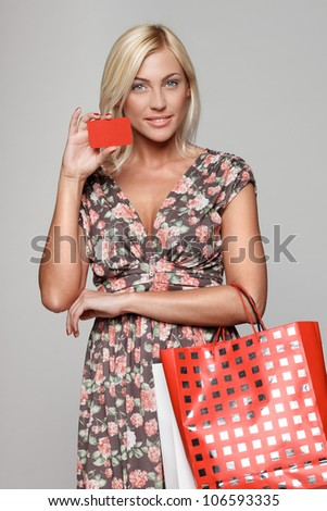 Happy shopping female holding blank credit card - stock photo