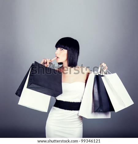 Happy shopping girl carrying new bags - stock photo