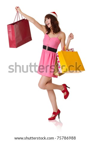 Happy shopping girl holding bags and wearing Christmas hat looking faraway, full length portrait isolated on white background. - stock photo