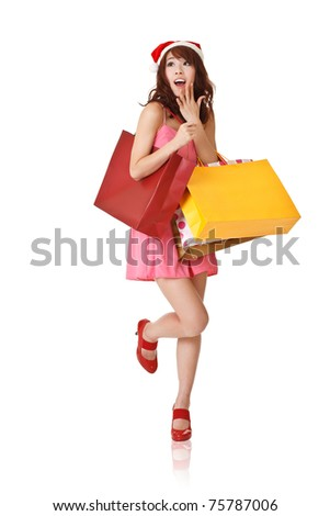 Happy shopping girl holding bags and wearing Christmas hat with surprised expression, full length portrait isolated on white background.