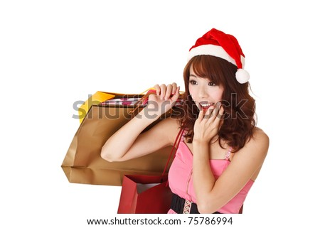 Happy shopping girl holding bags and wearing Christmas hat with surprised expression, half length closeup portrait on white background. - stock photo