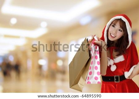 Happy shopping girl wearing Christmas clothes holding bags in department store. - stock photo