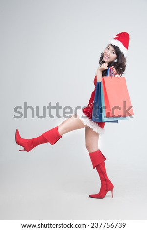 Happy shopping girl wearing Christmas clothes holding bags in department store,shopping, sale, gifts, christmas, x-mas concept - smiling woman in red dress and santa helper hat with shopping bag - stock photo
