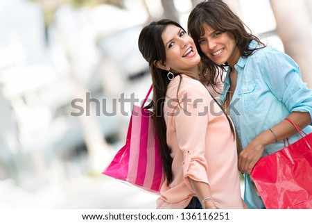 Happy shopping girls holding bags and smiling - stock photo