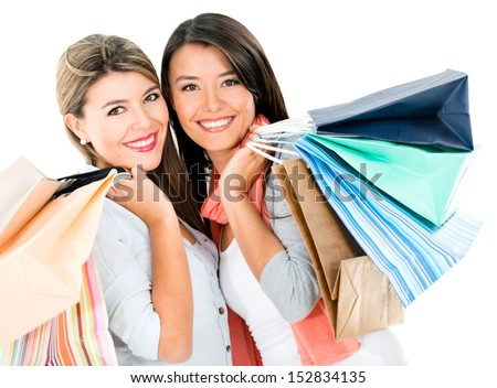 Happy shopping girls holding bags and smiling - isolated over white