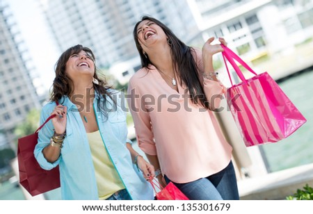 Happy shopping girls laughing and carrying bags - stock photo