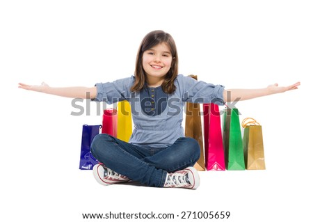 Happy shopping kid or young girl smiling satisfied of the shopping bags behind her - stock photo