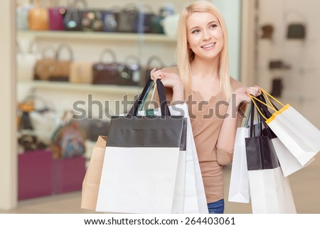 Happy shopping. Smiling and dreamy blond woman holding shopping bags in a shopping mall - stock photo