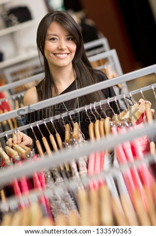 Happy shopping woman at a clothing store smiling - stock photo