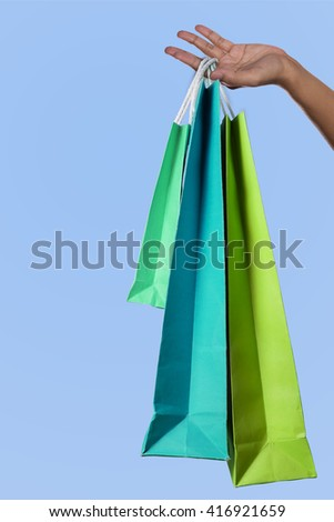 Happy shopping. woman hand holding multicolored shopping bags - stock photo