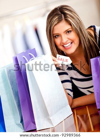 Happy shopping woman holding a sale tag