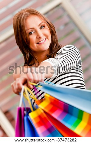 Happy shopping woman holding bags and smiling