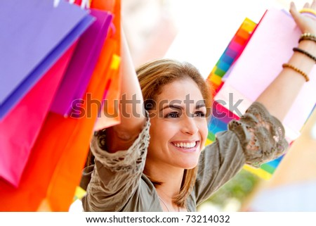 Happy shopping woman holding bags at a mall - stock photo