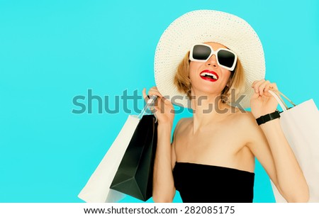 Happy Shopping Woman holding bags on blue background - stock photo