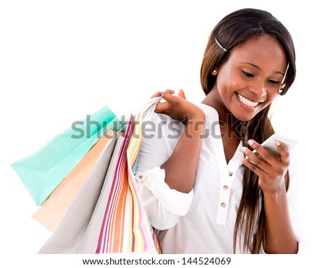 Happy shopping woman texting on her cell phone - isolated over white - stock photo
