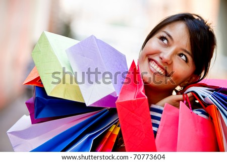 Happy shopping woman with bags and smiling - stock photo