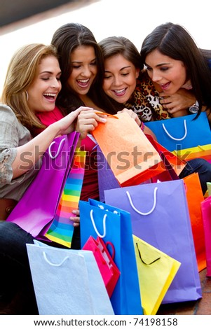 Happy shopping women looking into bags and smiling - stock photo