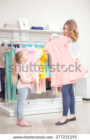 Happy shopping. Young mother showing a pastel pink dress to her small daughter in a boutique full length