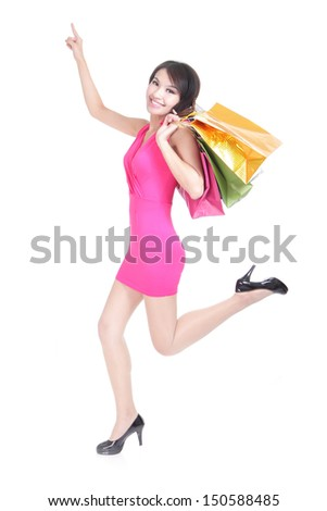 happy shopping young woman running and finger point to copy space with bags - isolated on white background, full body, asian model - stock photo
