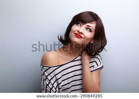 Happy short hair makeup woman thinking and looking up on blue background - stock photo